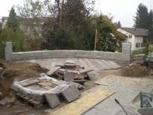 Sitzplatz im Garten mit Granitmauer und Porphyrsteinplatten auf Betonplatte. EFH in Möhlin.