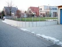 Abschlussmauer aus Winkelplatten mit Rundung für Einfahrt.