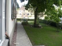 Neuer Pflasterweg ums Haus mit Schotterstreifen. MFH in Rheinfelden.
