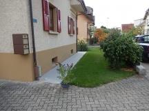 Gehweg ums Haus neu erstellt mit Gartenplatten aus Beton Rasenfläche angepasst und frisch angesät. Eschenmattstrasse in Möhlin.