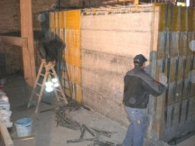 Schaltafeln entfernen von Betonwand im Hausinnern.